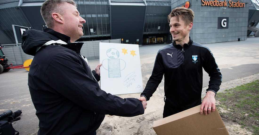 Markus Rosenberg lämnar över sitt konstverk till köparen Anders Johansson som vann auktionen i Sportbladets allsvenska fotbollsbibeln där pengarna gick till Cancerfonden. Totalt drog de allsvenska spelarnas tavlor in 87 505 kronor till organisationen.