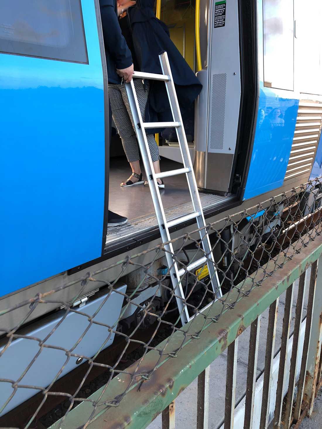 Tågvagnar står still på Skanstullsbron och resenärer klättrar över taggtråd och går på spåret för att ta sig därifrån.