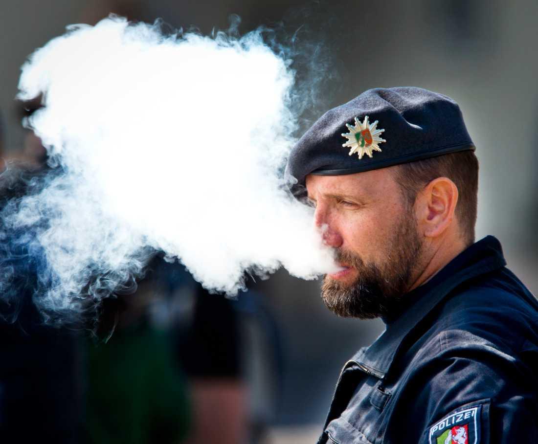 En polisman blåser ut rök från en e-cigarett under ceremonin då Karl Marx-statyn avtäcktes i tyska Trier på lördagen.