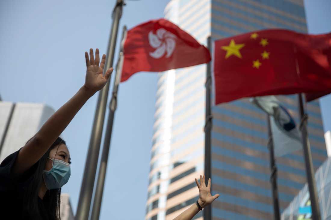 En demonstrant i Hongkong håller upp sin hand med sina fem fingrar som en symbol för de fem krav som demonstranterna ställt på Hongkongs regering.