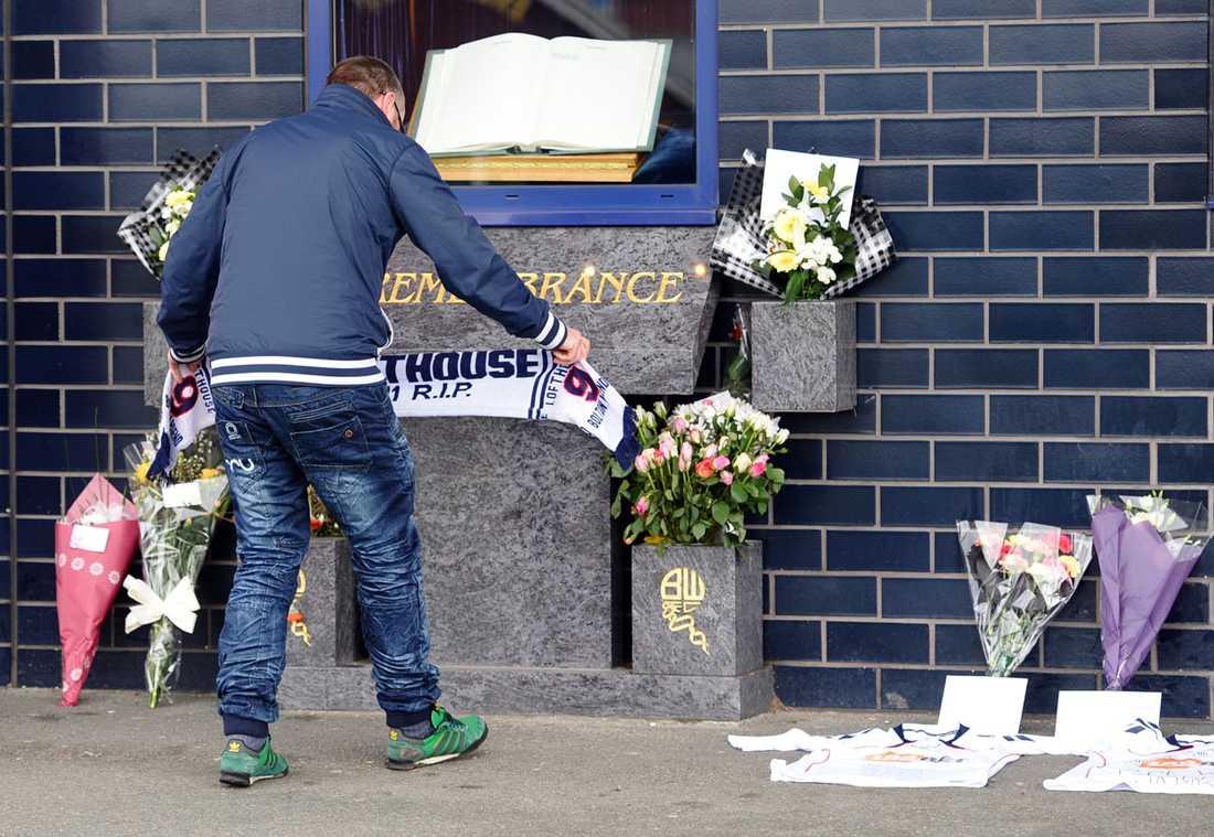 Ett fan lägger en sjal bredvid blommor och matchtröjor utanför Reebook Stadium i Bolton.