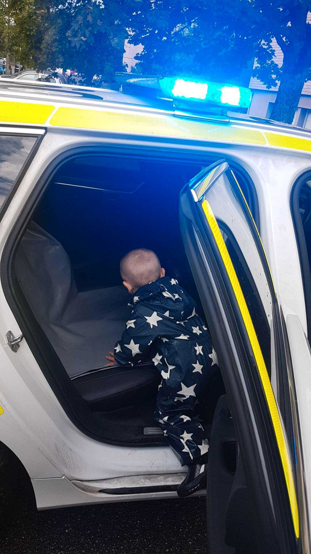 Pojken fick sitta i polisbilen.
