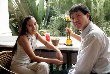 Lee Kit Pui med en Singapore sling tillsammans med Lei Jones som visar hur en singaporiansk Tiger-(öl) ska drickas på Raffles hotell.