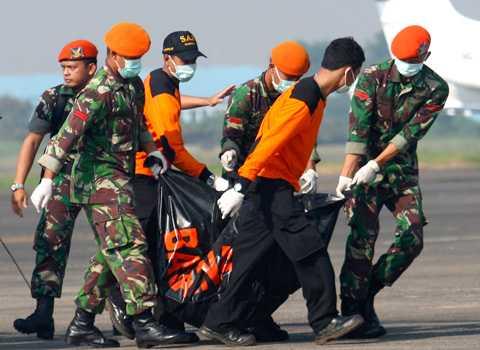 En av de tolv hittade kropparna bärs av soldater som deltar i sökarbetet.