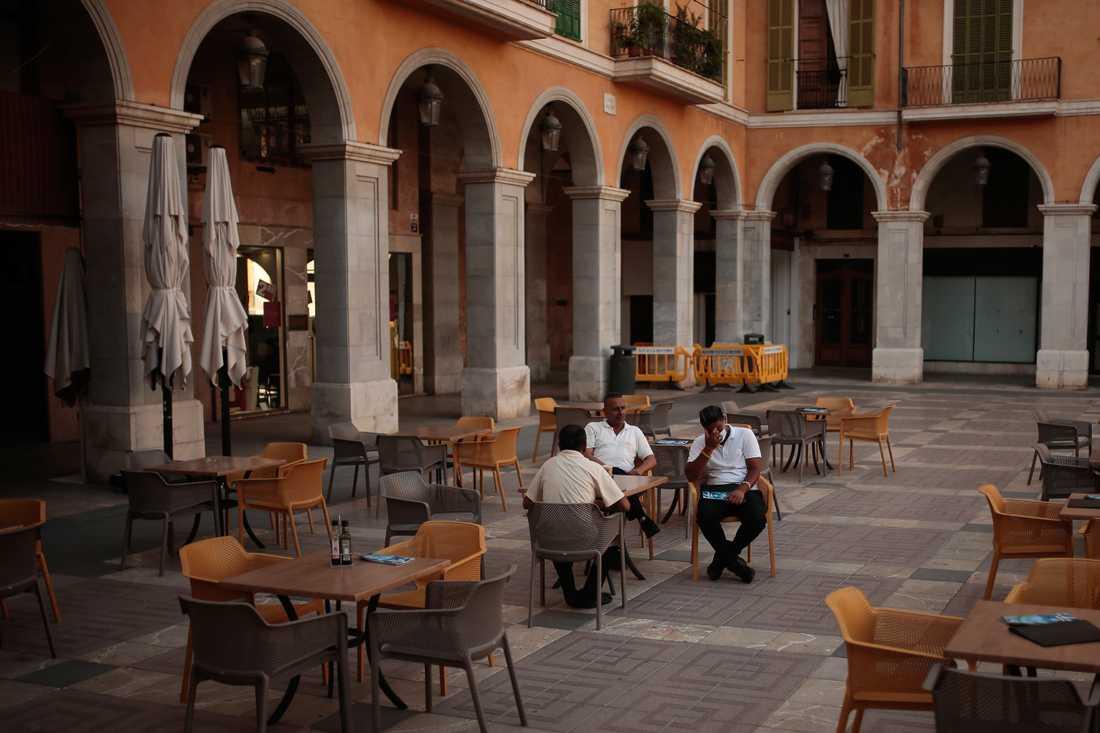 Män på ett folktomt restaurangtorg på Mallorca.