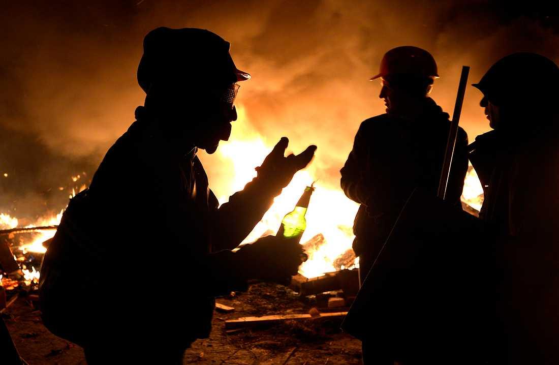 Unga killar tar risker och kastar molotov cocktails mot polis i skydd av rök.