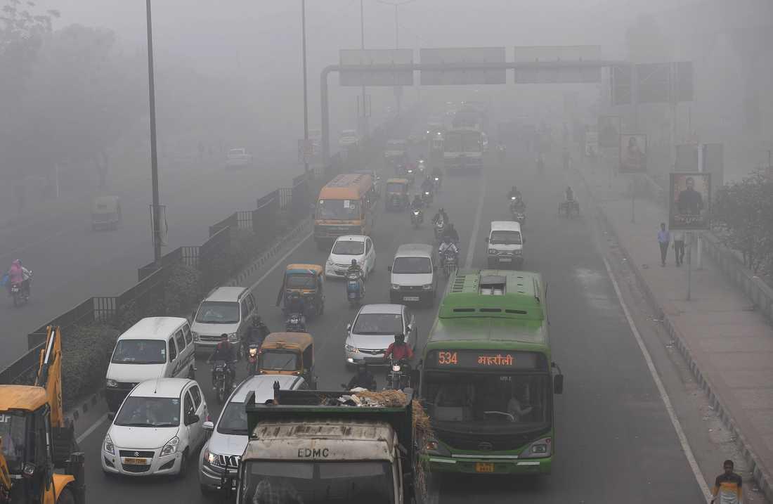 Rusningstrafik i smoggen i Dehli.