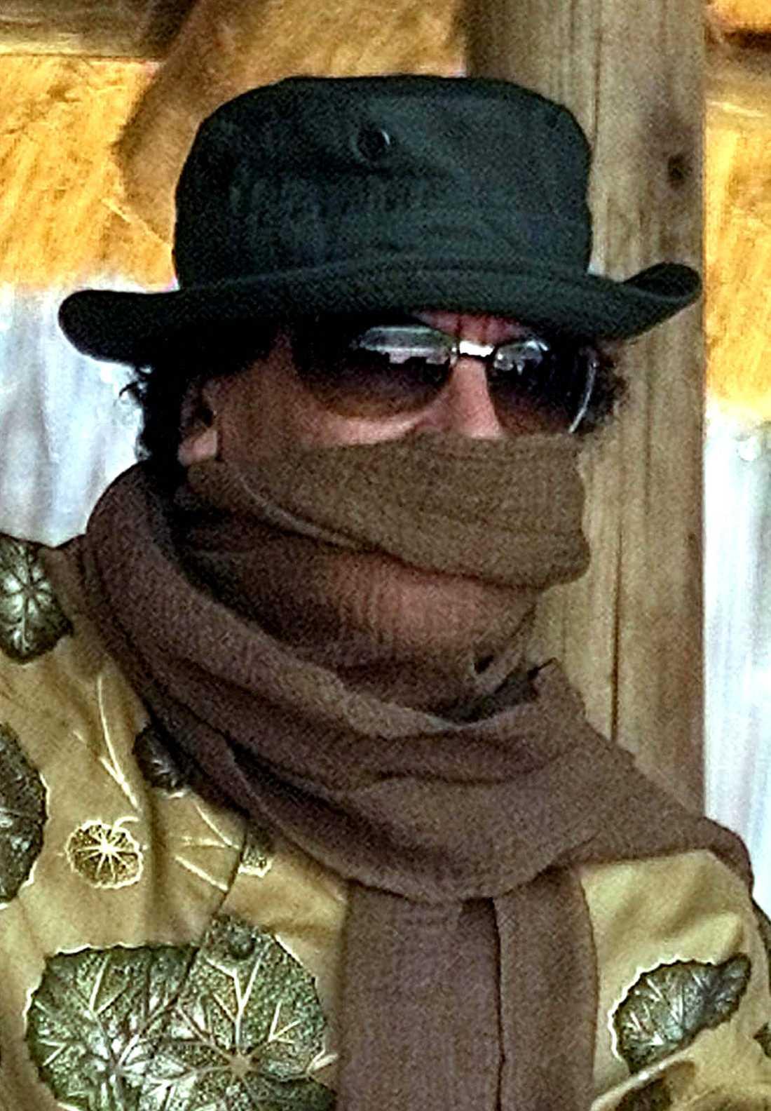 Muammar Gaddafi skyddar sig mot sanden med en scarf under ett besök i Swaziland.