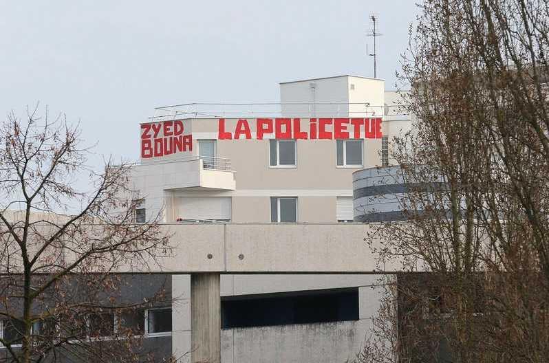 """Inför måndagens rättegång mot poliserna hade aktivister skrivit """"Zyed-Bouna: Polisen dödar"""" med stora röda bokstäver på en husfasad nära domstolsbyggnaden i Rennes. Foto: AP"""