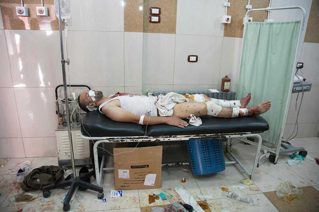 En man ligger skadad efter regimens bombningar. AFP PHOTO / THAER MOHAMMED / TT