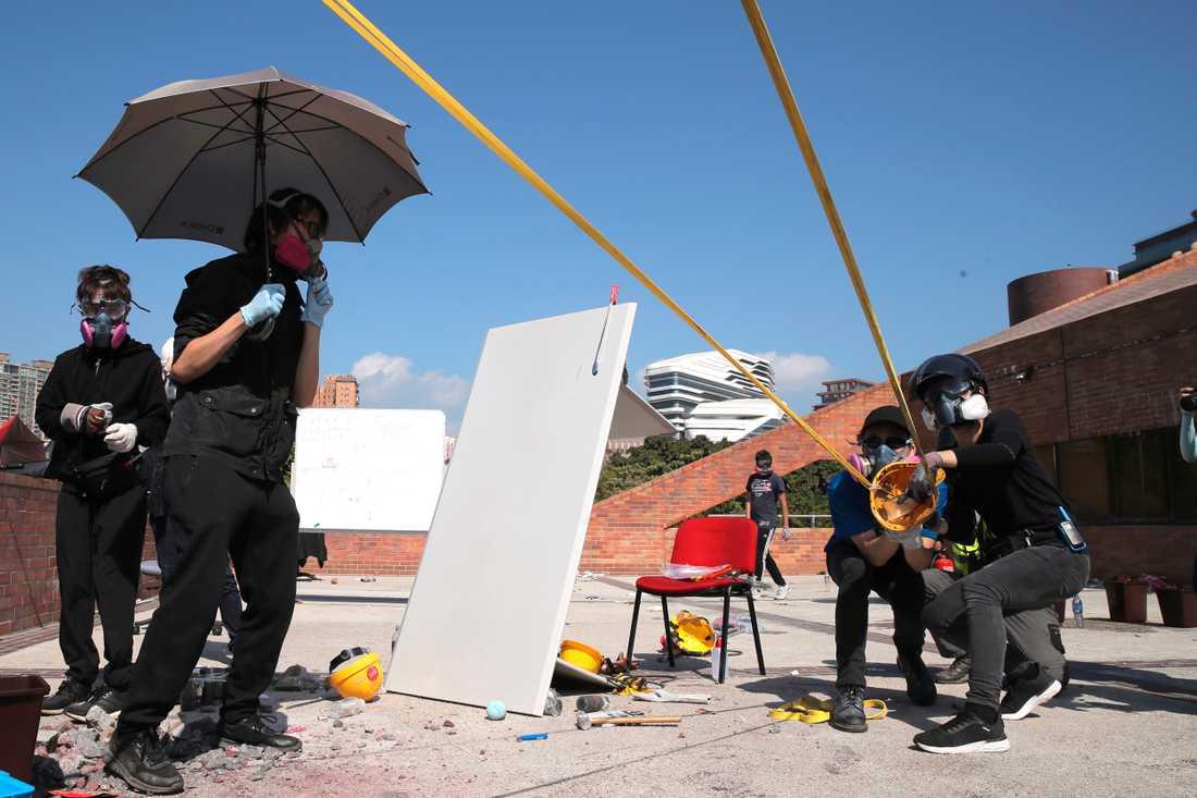 Demonstranter använder sig av jättelika slangbellor under sammandrabbningar med polisen.