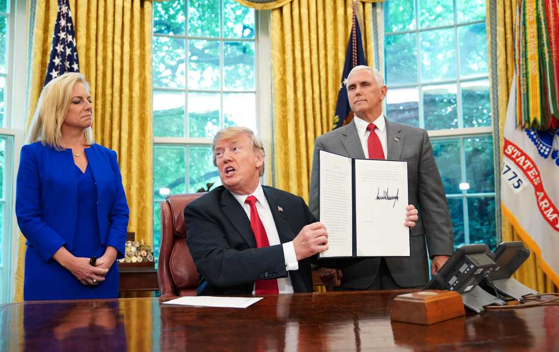 President Donald Trump håller upp den undertecknade ordern.