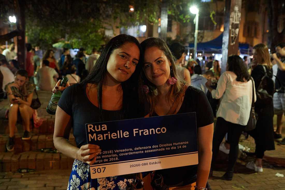 Mariana Souto, 31 (till vänster) ochElaine Martins, 33, håller upp en skylt med den i år mördade vänsteraktivisten och politikern Marielle Francos namn på.