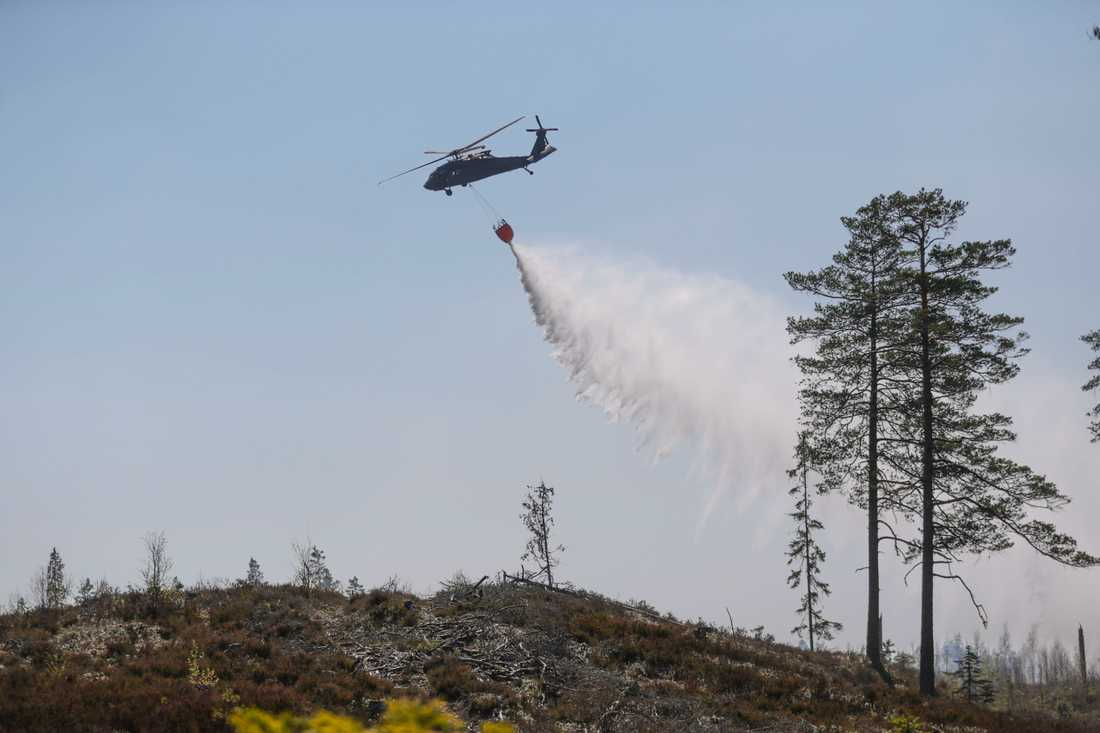 Försvarets helikopter hämtar vatten i en sjö för att vattenbomba en skogsbrand norr om Tjällmo, norr om Motala i Östergötland under tisdagen.