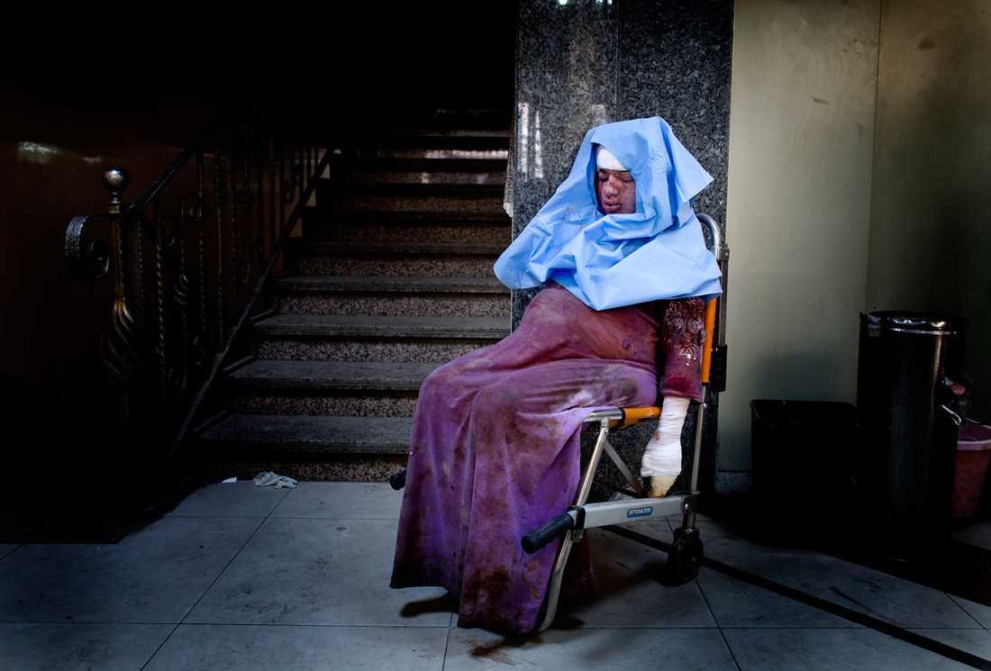 Den gravida kvinnan har skadats i en granatattack. Nu sitter hon avsvimmad på sjukhuset och väntar på vård.