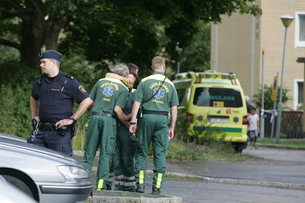 Chockad ambulanspersonal kramas om av en kollega.