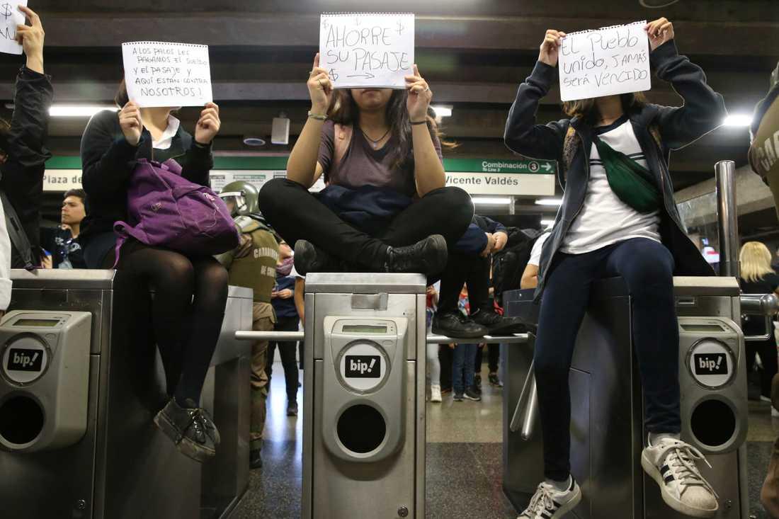 """En av de fredligare demonstrationerna. Studenterna håller upp skyltar med budskapen """"Vi betalar polisens löner och tunnelbanebiljetter och nu angriper de oss"""", """"Rädda våra biljetter"""" och """"Ett enat folk kommer aldrig att besegras""""."""