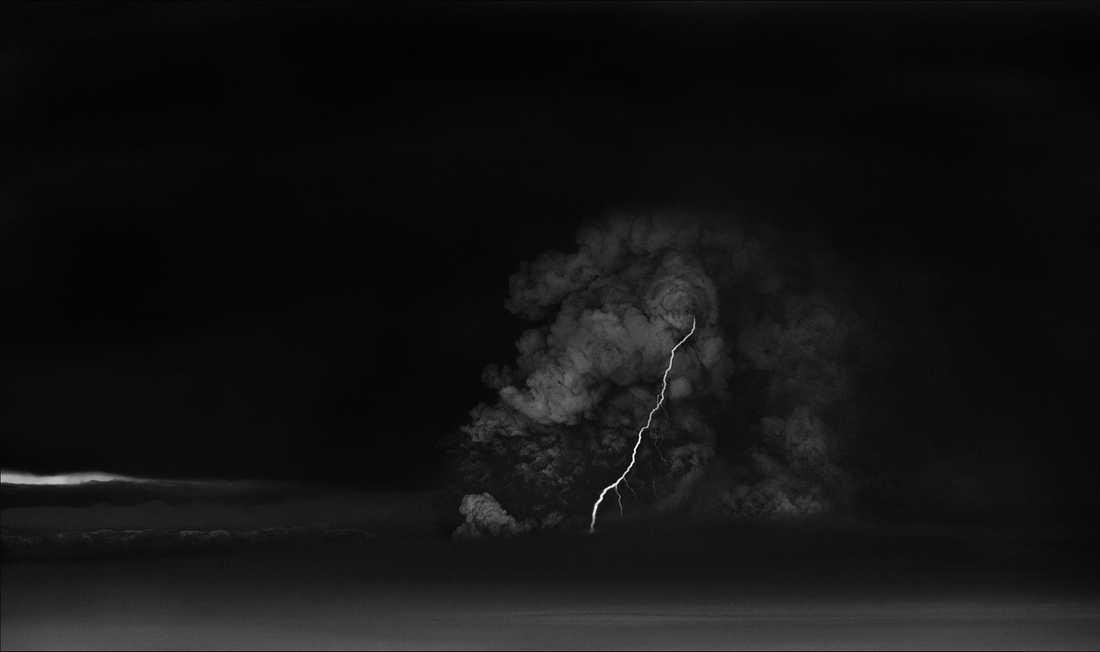 En blixt går genom ett tjockt moln av vulkanaska och rök.