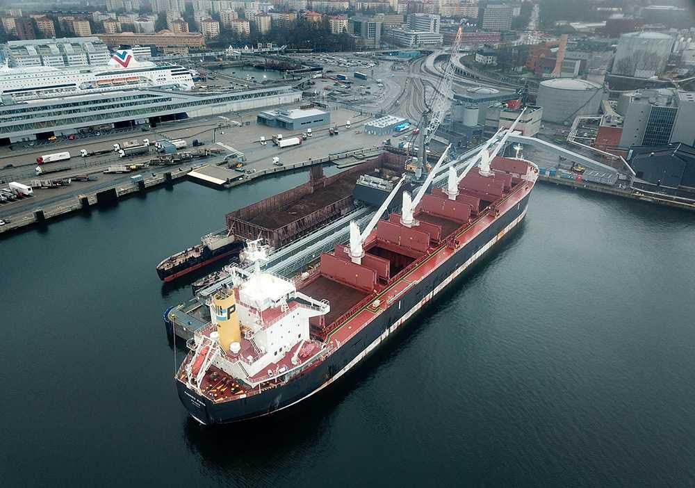 Bulkfartyget PHOENIX RISING ligger i Värahamnen och lossar flis från sydamerikas regnskogar som ska användas i värmeverket för att kunna värma frusna stockholmsbor.