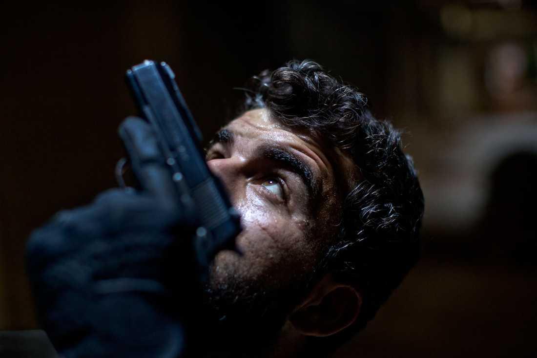 Abdullah Alyasin, soldat i rebellarmén, på utkik efter krypskyttar i Aleppos gamla stad.