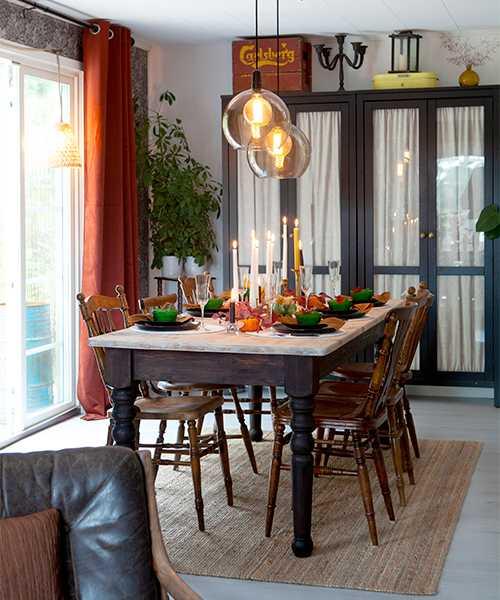 Jordiga kulörer i matsalen. Sammetsgardiner från Svanefors. Bord och stolar är köpta secondhand. Matta och taklampa från Ikea. Därifrån kommer också det stora skåpet som är köpt second hand på Blocket. Ovanpå står en gammal back från Carlsberg som passar perfekt till förvaring.
