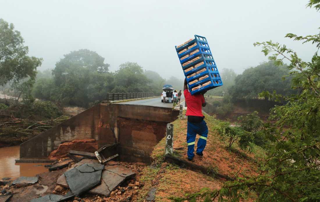 En man tar sig över en kollapsad bro i Chimanimani i Zimbabwe. Landets president har kallat cyklonen den värsta infrastrukturella katastrofen i Zimbabwes historia.