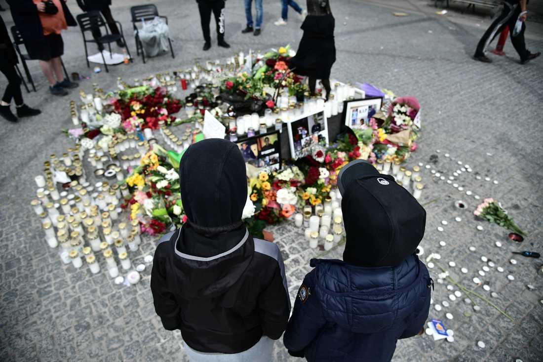De unga männen som mördats hedras med blommor och ljus på torget i Sätra centrum.