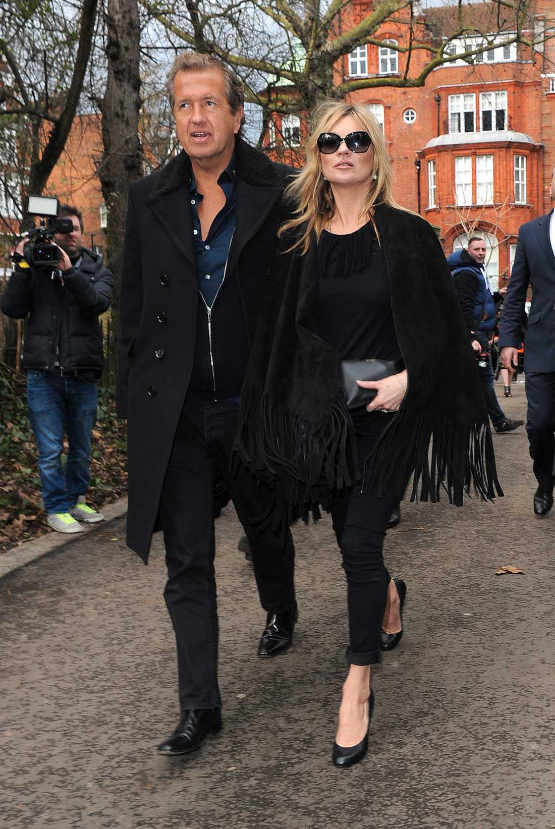 Kate Moss Supermodellen är lika snygg som vanligt i en svart look med fransad cape.