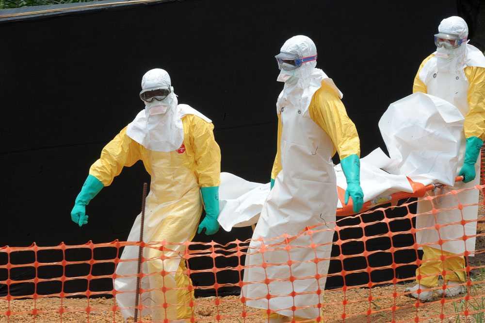 Läkare utan gränser med en person som dött av ebolaepidemin i Guinea.