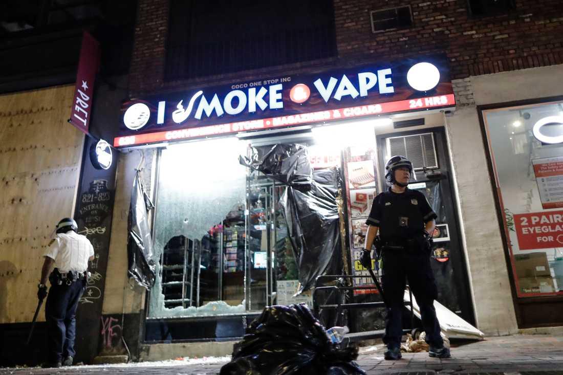 Polis bevakar en plundrad butik i New York.
