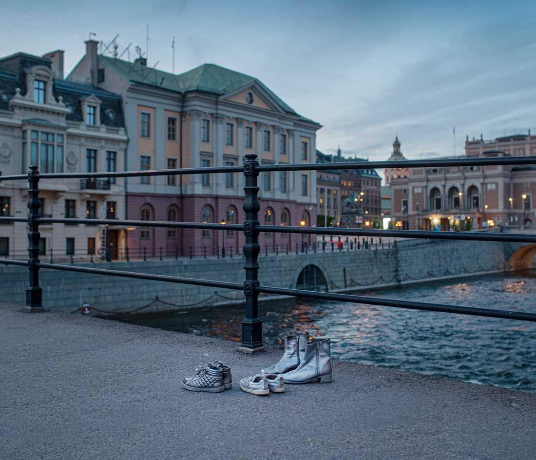 """Gömda kvinnor placerar ut skor på valda platser för att uppmärksamma de kvinnor och barn som tvingas hålla sig gömda och leva med dold identitet på grund av våldsamma män. Skor på Riksbron framför Sagerska palatset. Aktionen """"Gömda och glömda""""."""