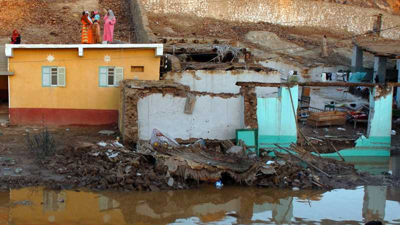 Kvinnor räddar sig upp på hustaken i skydd från vattenmassorna nära staden Assuan i Egypten.