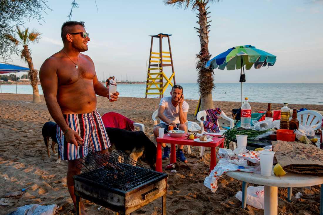 Johnny och hans kompisar sitter och grillar längs Atens strandremsa. Han skrattar åt norra Europas okunskap om grekerna. – Att vi hänger på stranden, grillar och har kul på kvällen betyder inte att vi är lata, säger han och fortsätter: – Jag säljer knark. Haha, nej det gör jag inte. Jag jobbar på en bensinmack.