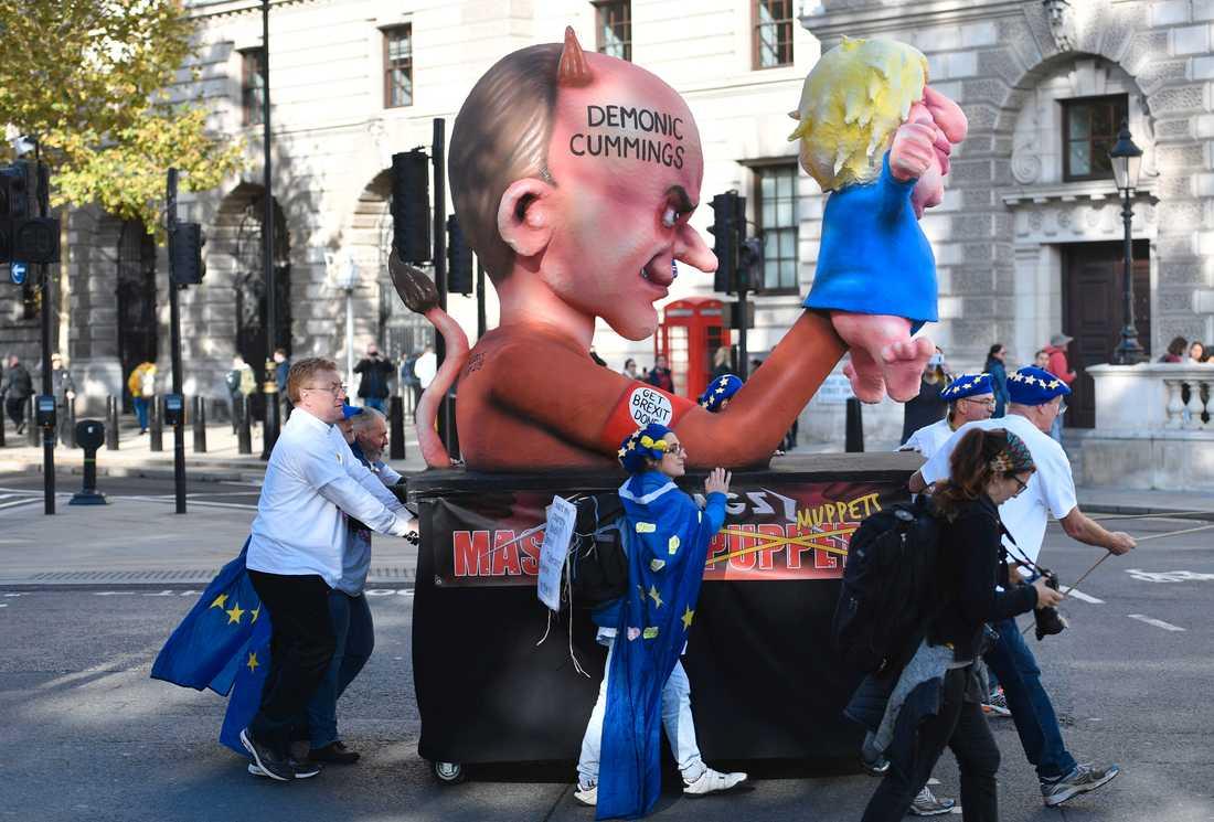En figur föreställande rådgivaren Dominic Cummings som håller i en kasperdocka som föreställer premiärminister Boris Johnson. Bilden är tagen under en protest anordnad av brexitmotståndare. Arkivbild.