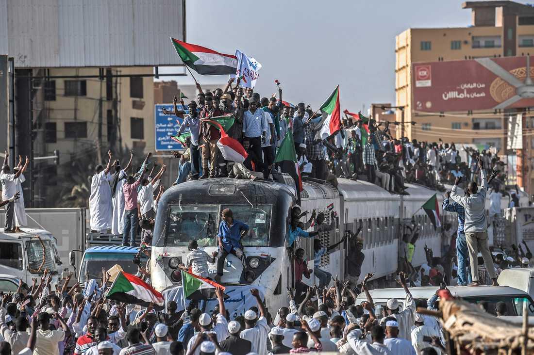 Demonstranter som kommer med tåg till Sudans huvudstad Khartum tas emot av jublande likasinnade.