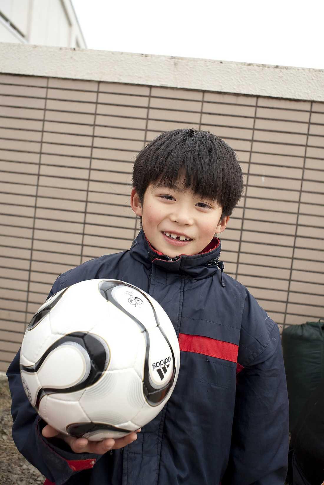 skiner upp I kriscentrumet i Ishinomaki serverades i går för första gången ett mål varm mat. Shota Saito, 9, är trött och hängig – men skiner upp när han får en fotboll.