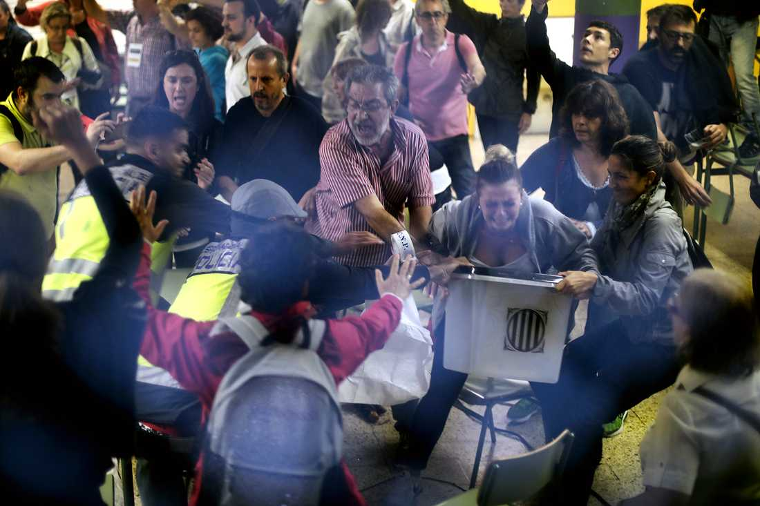 Civilklädd polis försöker ta en valurna vid Ramon Llull school i Barcelona.