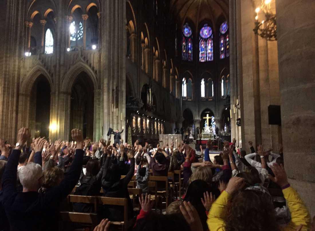 Människor inne i katedralen höjer armarna under pågående drama på polisens uppmaning.