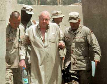 CELLKAMRATEN FRIGIVEN Ulf Hjertström förhördes under tre dagar om tiden som gisslan. Hans detaljerade vittnesuppgifter hjälpte till att frige australiensaren Douglas Wood, som också kidnappats och i flera veckor delade cell med svensken. Här eskorteras Douglas Wood av amerikansk militär efter frigivandet den 15 juni.