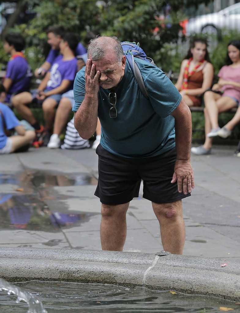 En man svalkar sig med vatten från en fontän i New York.