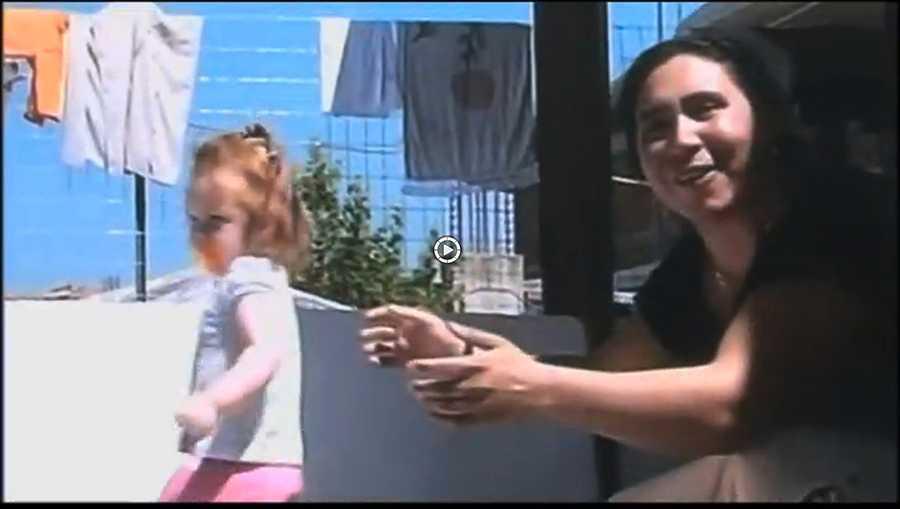Kvinnan applåderar och ler in i kameran.