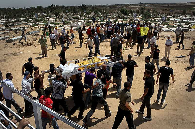 En hel procession av pojkar och män följer Nael till begravningsplatsen på de öppna fälten mot den israeliska gränsen.