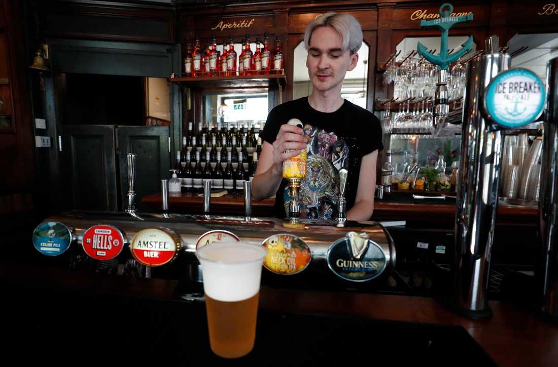 En bartender häller upp en öl på The Crabtree Pub i London på tisdagen. Handgreppen har inte gått förlorade under nedstängningen.