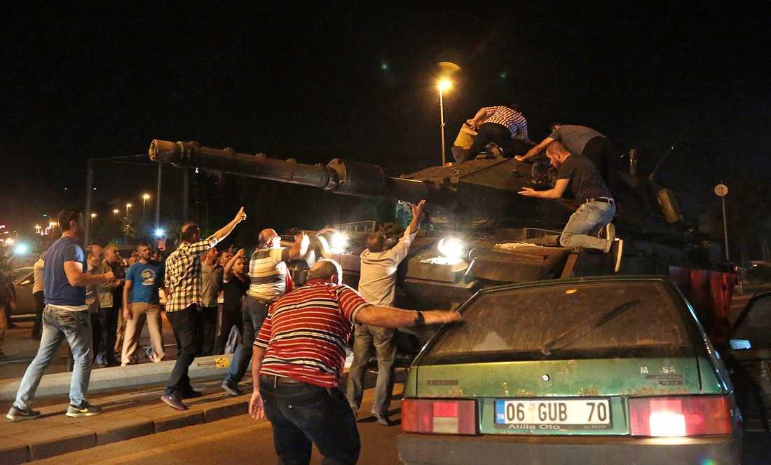 Människor stormar en pansarvagn i protest mot militärkuppen.