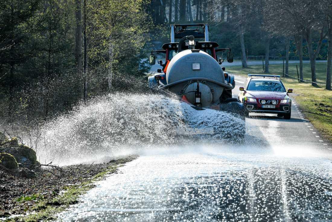 Med hjälp av traktor och gödseltank vattenbegjuter man vägarna i skånska Hästveda.