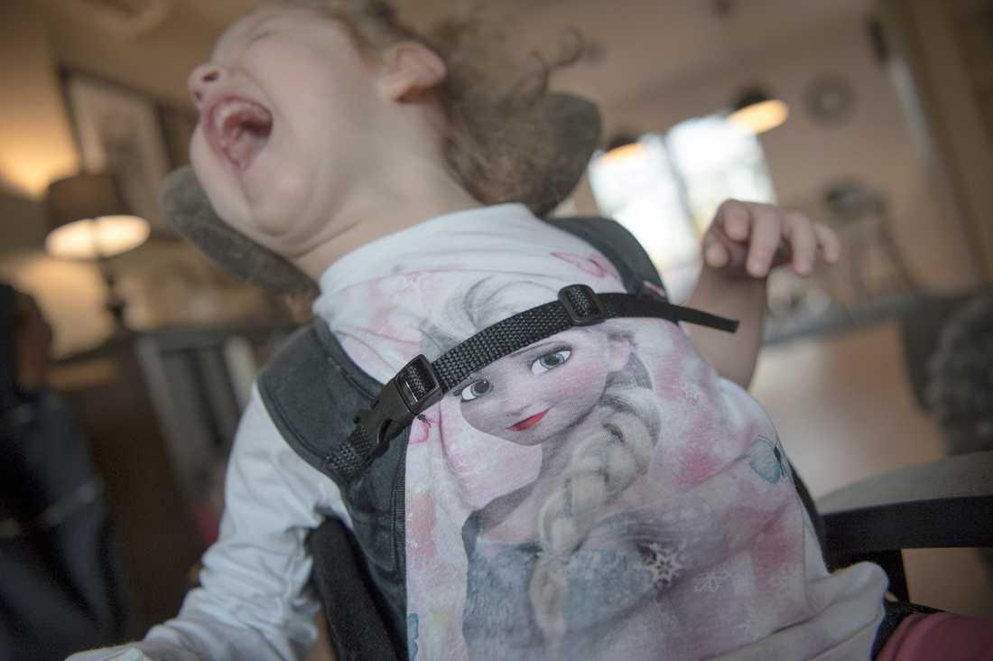 Elvira, 2,5, har även epilepsi och är svårt spastisk. Hon har ofrivilliga rörelser och kroppen spänner sig ofta bakåt i en båge. Hon har en specialanpassad rullstol med fjädrande rygg-och nackstöd.