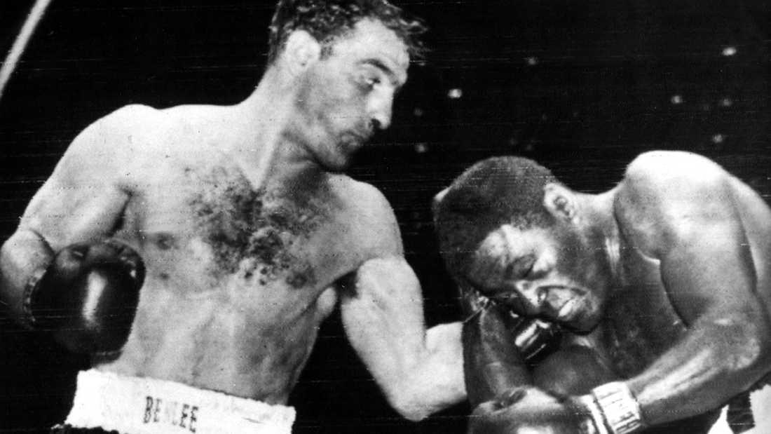 Rocky Marciano (1923-1969) får in en träff på Ezzard Charles (1921-1975) i juni 1954. Massachusetts-sonen Marciano hade italienskt ursprung, innehade världsmästarbältet 1952-1956 och är den ende tungviktsmästaren som dragit sig tillbaka utan att förlora en enda match.