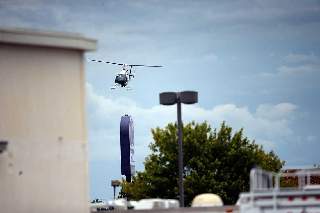 En polishelikopter cirkulerar över platsen.