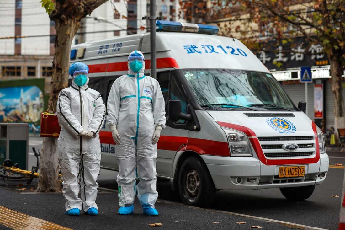 Ambulanspersonal i skyddsutrustning väntar på en patient vid ett bostadsområde i Wuhan.