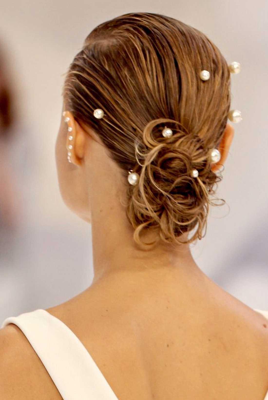 """chanel. Sno partyfrippan från modellerna på Chanels vårvisning! Slätkamma håret till en frissfri backslick och fäst i en tofs som sveps upp till en knut. Dekorera med stora pärlor uppträdda på hårnålar. Ett utslätande serum tämjer småhår och kluvna toppar, testa """"Absolut repair cellular treatment serum"""" ur serien """"Série expert"""" från L'Oréal Professionnel för 180 kronor."""